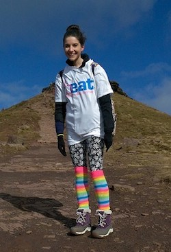 "Picture of a young white woman with dark hair tied up with a large clip at the back of her head, wearing a white T-shirt with the logo ""Beat eating disorders"", a rainbow-striped pair of long socks and a pair of black leggings with a white flower pattern on them."