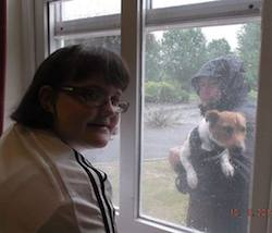 Picture of Claire Dyer, a young white woman with shoulder-length hair, looking through a closed window at her dog, Jonjo, who is being held up to the window by a person in a black raincoat.