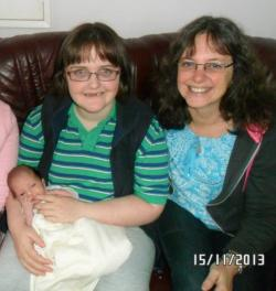 Picture of Claire Dyer, a young white woman wearing a green and blue striped T-shirt, holding a young baby, next to her mother, Cath Dyer, a white woman with shoulder-length dark hair wearing a light blue top and a black jacket over it.