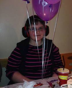 Picture of Claire Dyer, a young white woman wearing a black and red striped jumper with headphones on (to cancel out noise). She has purple Pizza Hut balloons above her head and the strings are in front of her.