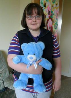 Picture of Claire Dyer, a young white woman with shoulder-length dark hair and a sunken face, wearing a black sleeveless jumper over a striped top, holding a bright blue teddy bear.
