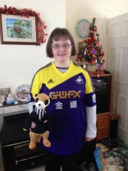 Claire Dyer, a young white woman, wearing a yellow and blue Swansea FC shirt, holding a black and brown cuddly toy, in front of a fireplace with a miniature Christmas tree on her right