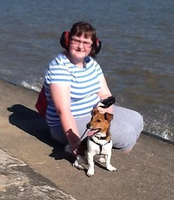 Claire (a young white woman wearing a stripey white and blue top and grey tracksuit bottoms, wearing red and black ear defenders) sitting on a beach with a small brown dog.