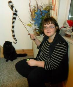 Picture of Claire Dyer, a young white woman with neck-length dark hair wearing a black top with white stripes and black trousers, sitting on the floor holding a stick with a sock dangling from it, with a black cat to her left, at the bottom of some stairs.