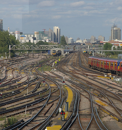 A large rail junction with several lines, all of them electrified with third rails, with a train wash with a train passing through it, and a passenger train with Stagecoach red, orange and white livery on the right.