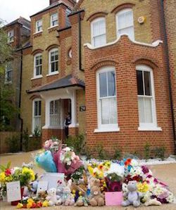A picture of a three-storey yellow- and red-brick house, with flowers and teddy bears left in the driveway to the front