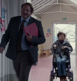 A stockily-built white man in a suit walking down a corridor in an institutional building carrying a red folder under his arm, followed by a white woman in a powered wheelchair wearing a grey overcoat and a pair of blue jeans.