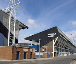 "A picture of a street with a football stand backing onto it, with ""Cobbold Stand"" and ""Ipswich Town Football Club"" on the sides, and shops fronting onto the street. Another stand is to the left with turnstiles below."
