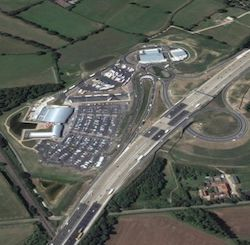 An overhead view of the Cobham service area on the M25 motorway. A junction has been built to allow traffic from both sides of the motorway to access the services.