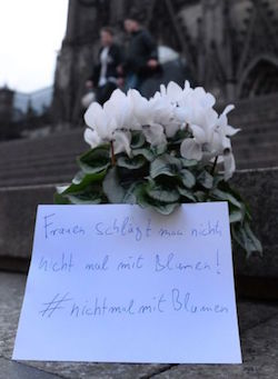 "A picture of some white flowers left on the steps of Cologne cathedral, with a message in German, ""one does not hit women, even with flowers"". Two people, perhaps a couple, are walking down the steps behind."