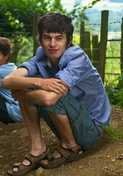 Picture of a young white man wearing a blue shirt and blue jean-shorts, sitting in a squatting position with his hands around his knees, on muddy ground in front of a wire fence, behind which is a green field.