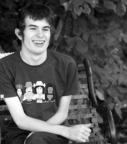 Black and white picture of Connor Sparrowhawk, a young white man with dark, tousled hair with a T-shirt with four cartoon figures on it. He has a wide smile on his face.