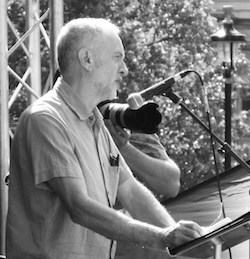 Black and white picture of Jeremy Corbyn taken from the right, standing in front of a lectern with a microphone, with a camera pointing towards the audience from his left.