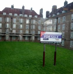 "PIcture of a five-storey, red-brick building with a courtyard, with a ""For Sale"" sign at foreground"