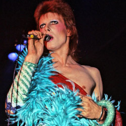 Picture of David Bowie from 1973; a picture of a white man in a red top with a turcquoise feather thing wrapped round his chest, and various other brightly-coloured accoutrements.