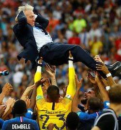 Didier Deschamps, a clean-shaven white man wearing a navy blue suit with a white shirt underneath, is raised into the air by a group of football players of mostly African and Arab appearance. The names Areola and Dembele are visible on the backs of two of the players in the foreground. Blurred, the crowd can be seen in the background.
