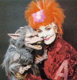 Picture of Helen A, a woman (played by Sheila Hancock) with bright orange hair, a red jacket with a large letter A emblazoned on the arm, holding a 'stigorax', a vaguely dog-like animal with grey hair