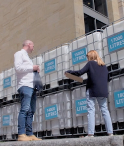 "Stacey Dooley, facing away from the camera wearing a blue cardigan and loose, light blue jeans, standing in front of a row of industrial water containers made of plastic inside a metal cage, each with a sign on them saying ""13,000 LITRES"", ""14,000 LITRES"" or whatever, talking to a balding white man in a white shirt and blue jeans, holding a shopping bag in his hand."
