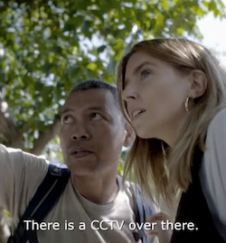 "Stacey Dooley, a young white woman with blonde hair wearing a white top with a dark blue or black sleeveless top over it, in conversation with a south-east Asian man with very short hair. A tree is out of focus in the background. The words ""There is a CCTV over there"" can be seen at the bottom."