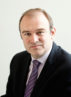 Picture of Ed Davey, a middle-aged white man wearing a white-ish shirt, a patterned tie and a dark jacket.