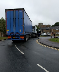 The back of an articulated lorry consisting of a low-height, white Iveco tractor unit coupled to a long, 15ft 3in high trailer with blue curtain sides. The truck is on a bend, the tractor is over to the left while the back of the trailer is about halfway over the other side of the road.
