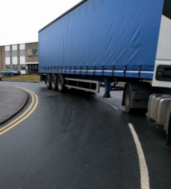 A blue curtain-sided trailer halfway round a tight corner on a road.