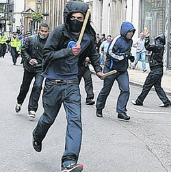 Picture of a man with his face partly covered, carrying a bat of some kind, with police in the background