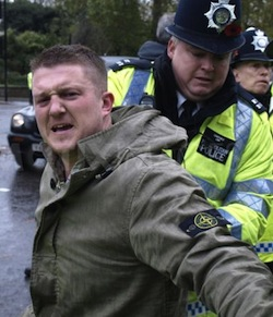 Picture of Tommy Robinson, a clean-shaven white man with an aggressive look on his face, being arrested by a London police officer