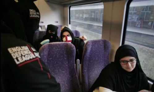 "Picture of a Muslim woman in a black hijab on a train, with masked men with ""English Defence League"" badges on their clothes"