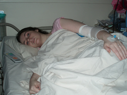 Picture of Emily Collingridge, a white woman lying on her side in a hospital bed covered in white sheets. She has an obviously distressed look on her face/