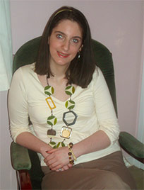 Picture of Emily Collingridge, a young white woman with shoulder-length brown hair, wearing a cream colour T-shirt wiht a long necklace of ornaments and a thick bracelet