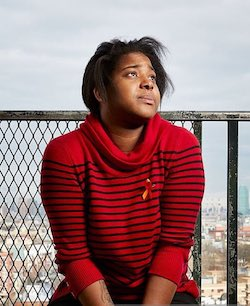 Picture of Erica Garner, a Black woman wearing a red sweatshirt with thin black horizontal stripes running across it. She also has a red ribbon pinned to her chest.