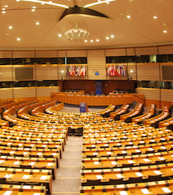 Picture of the chamber of the European Parliament in Brussels. Seats are arranged in a semi-circle with an aisle separating them. A lectern is at the front with a blue backing; a row of 11 seats faces the semi-circle with a high-backed seat in the middle. A small EU flag hangs on the wall at the back, and larger, furled-up flags of the member states hang on either side of it.