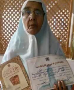 Fatimah Ouaziz, holding her school textbook and grade certificate