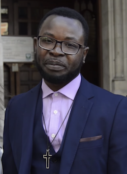 Picture of Felix Ngole, a young Black man with short black hair wearing a dark blue blazer over a dark blue waistcoat over a light purple shirt with a large cross hanging from a string around his neck