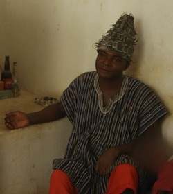 An African man wearing a tall hat, a striped grey tunic with red trousers, with his right arm resting on a stone surface next to him