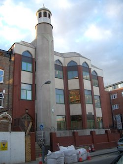 Finsbury Park mosque, a red-brick mosque with a grey concrete minaret. Some bags of aggregate are sitting outside and the next door house has a hoarding outside it.