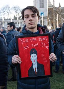 """A man standing on grass holding a sign bearing the words """"For the many, not the Jew"""" in white on a red background."""