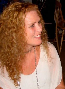 Picture of Frances Andrade, a white woman in her 40s with long curly hair, wearing a white T-shirt.