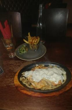 a large piece of chicken surrounded by fried onions and with a mushroom sauce on top, on a black plate on top of a wooden plate; behind it is a portion of potato chips in a metal mesh container with a long handle, on a plate with a small portion of salad. A glass of water to the left with a bottle of water behind the plate with the chips on. Behind the glass of water is a container with three pairs of knives and forks wrapped in a red paper tissue.