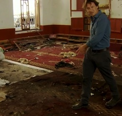 Gabriel Gatehouse, a white male TV reporter wearing a blue shirt and black trousers, walking through a mosque with a red carpet strewn with debris left by a suicide bombing