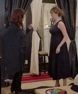 Two women in a clothing shop, one of which is trying on a long, black, sleeveless dress with a fitted bodice and a full skirt.