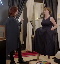 Two white women in a clothing store; the woman wearing the black dress now has her hands in the dress's pockets and is holding the skirt out with an excited look on her face.