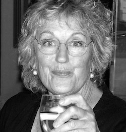 Black and white picture of Germaine Greer, an older white woman wearing a black top, holding a glass of some drink in her hand