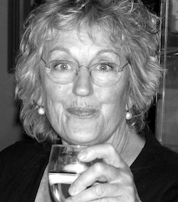 Black and white picture of Germaine Greer, an elderly white woman with glasses, holding a glass of drink.