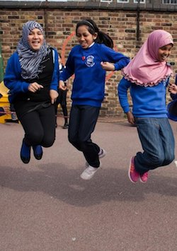 Three girls aged about 10 or perhaps less, jumping over a skipping rope. All are of South Asian appearance, wearing a blue school uniform jumper with black or blue trousers. The girl on the left has a black and white patterned wrap-around hijab; the girl on the right has a pink wrap-around hijab, while the girl in the middle is not wearing one. A brick wall with an orange hoop painted on it is behind them
