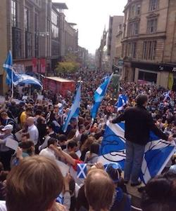 A demonstration in favour of a Yes vote in Glasgow, today (13th September 2014); people are filling a street and there are Scottish flags being held in the foreground