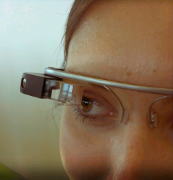 Detail of a Google Glass prototype, showing an ear-and-nose-mounted headset with a camera and screen mounted over the right eye.