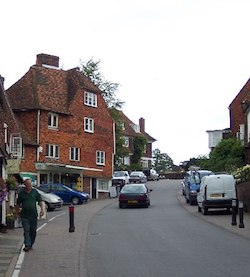 A picture of a main road through a village which is not wide enough for two cars to pass or to justify putting a line down the centre. A four-storey red-brick house is to the left of the road with a pharmacy on the ground level. A car is making its way up the road (on the left side) and other cars are parked on the pavements on each side.