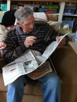 Picture of an elderly white man with a grey patterned jumper, reading the Observer with a magnifying glass